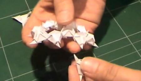 mãos manipulando o origami