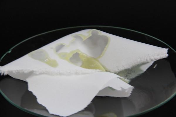 tecido de algodão com gotas de ácido sulfúrico concentrado em um vidro relógio