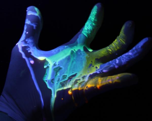 mão com luva e líquido que brilha no escuro