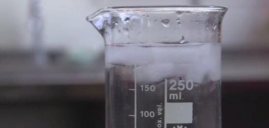 gelo flutuando em um bequer com agua liquida