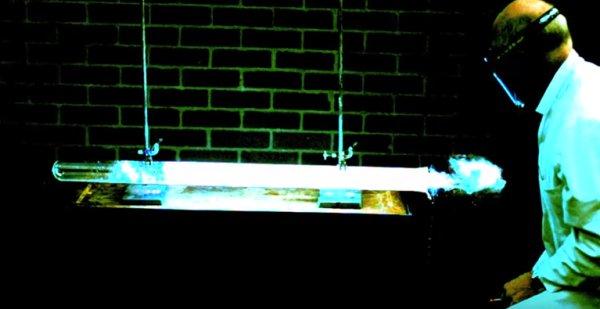 tubo horizontal com gas brilhando e cientista com roupa de proteção