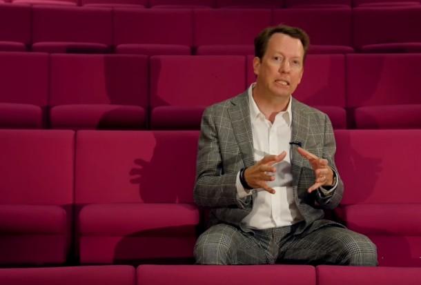 homem sentado em cadeiras de um auditório